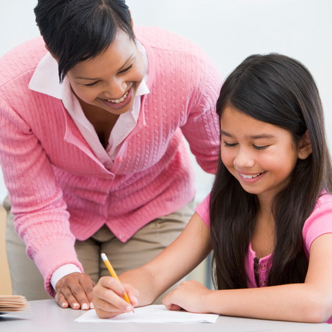 Teacher helping pupil with written project sitting at desk smiling