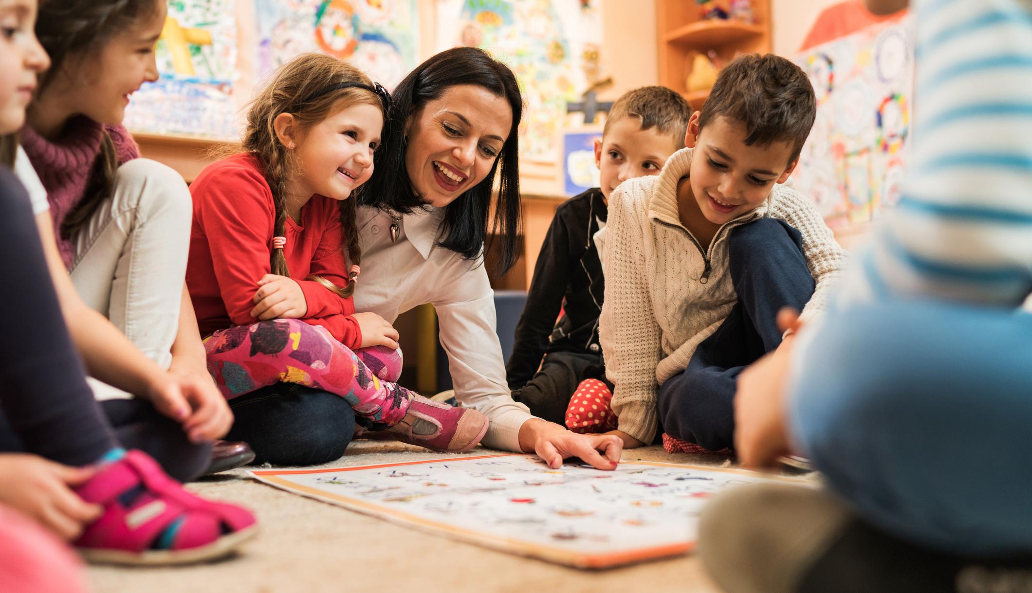 Happy preschool teacher educating large group of children in kindergarten.
